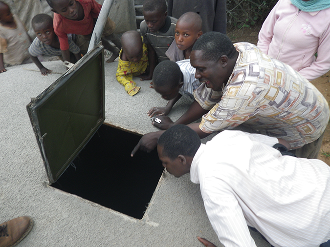 People gather to inspect Claude's water storage tank behind his milling plant. © Louise Bloom.