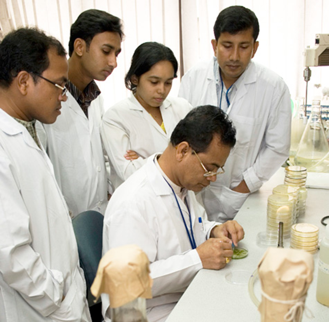 Dr. Md. Sirajul Islam (centre) shows his team how to test an algae sample for Cholera. © icddr,b