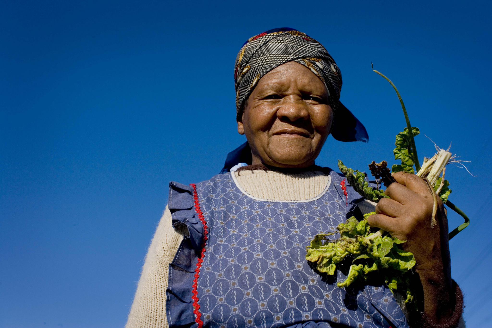 A woman holds up some of the vegetables she has grown in a garden in Cape Town, South Africa. © Kate Holt/Africa Practice