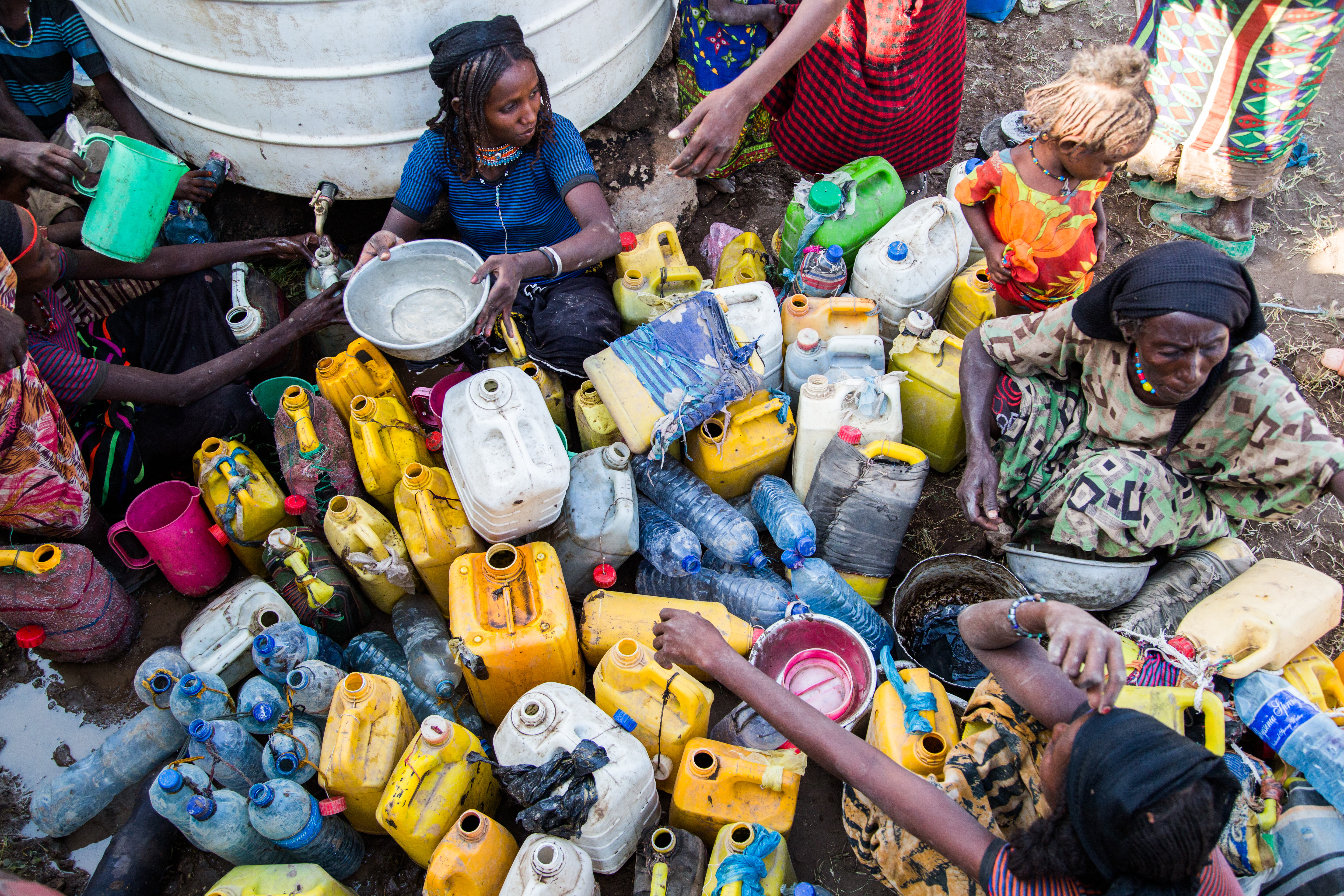 Huseyna Faraha, 20 years old, helping others in pouring water in their containers. Credit: UNICEF Ethiopia