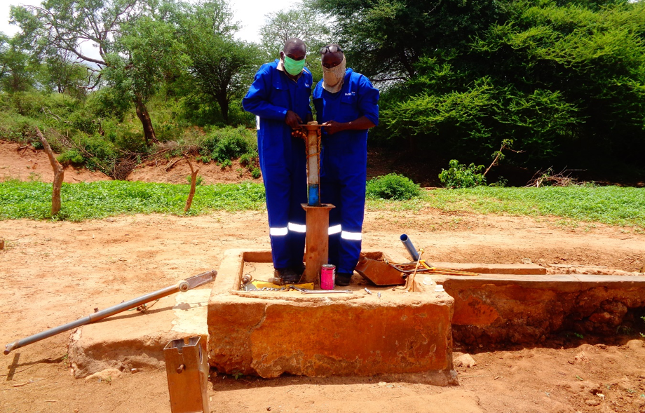 Fundifix mechanics wearing masks while fixing a handpump. Credit: Musenya Sammy