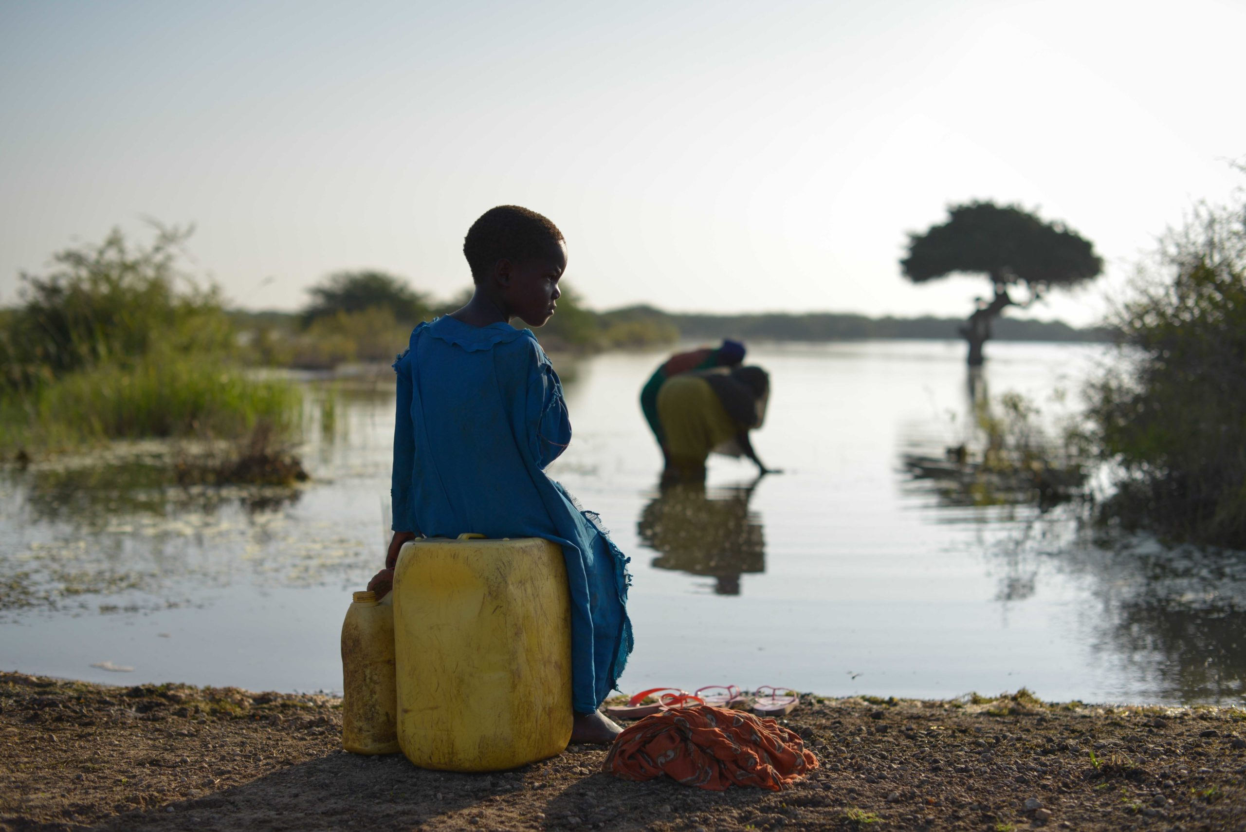 A young girl sits on a jerry can, as her mother fills up another with water, near the town of Jowhar, Somalia, on December 15. The area around Jowhar has experienced large amounts of flooding this year, completely blocking off the town from main roads and forcing thousands to flee their homes and seek shelter on higher ground. AU UN IST PHOTO / Tobin Jones