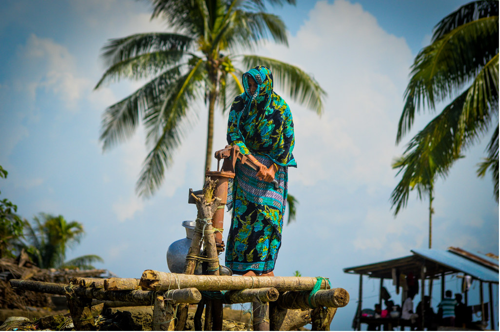 A woman drawing water from a hand pump in Bangladesh